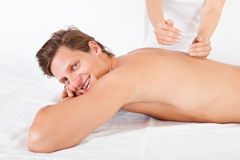 Man Getting Spa Treatment. Shirtless Man Lying On Front Getting Spa Treatment Royalty Free Stock Photos