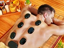 Man getting stone therapy massage . Man getting stone therapy massage in bamboo spa Royalty Free Stock Images