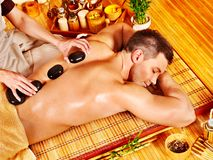 Man getting stone therapy massage . Man getting stone therapy massage in bamboo spa Stock Photo