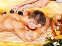 Man getting stone therapy massage . Man getting stone therapy massage in bamboo spa Royalty Free Stock Photo