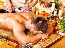 Man getting stone therapy massage . Man getting stone therapy massage in bamboo spa Stock Image