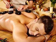 Man getting stone therapy massage . Man getting stone therapy massage in bamboo spa Royalty Free Stock Photos