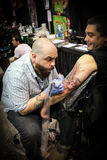Man getting tattoo on arm Royalty Free Stock Photography