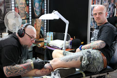 Man getting a tattoo, at a tattoo studio. Tattoo artist at work at tattoo parlor royalty free stock images