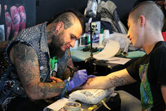 Man getting a tattoo, at a tattoo studio Stock Images