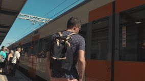 Man getting on train. Casual guy with a backpack getting on a train from a station, travelling alone. Modern train come on station stock video footage