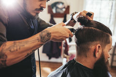 Man getting trendy haircut in barber shop. Close up shot of men getting trendy haircut at barber shop. Male hairstylist serving client, making haircut using Stock Photography