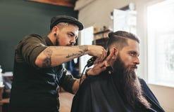 Man getting trendy haircut in barbershop royalty free stock photos
