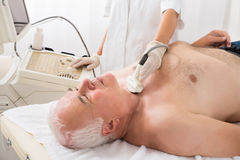 Man Getting Ultrasound Scan On Neck By Doctor. Senior Man Getting Ultrasound Scan On Neck By Young Female Doctor Royalty Free Stock Photo