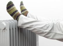 A Man Getting warm in cold winter days. Two feet placed on a heater for warmth. A Man Getting warm in cold winter days. Two feet placed on a heater for warmth Royalty Free Stock Photos