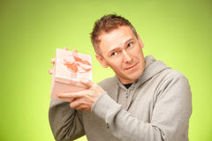 Man with gift. Cheerful man guessing what's inside his birhday gift box Royalty Free Stock Images