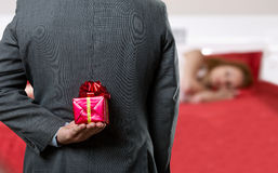 Man with a gift behind his back Stock Images