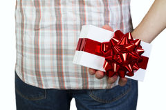 Man with gift box behind back. Man holding gift box in red ribbon behind back Royalty Free Stock Photo