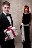 Man with a gift box and girl behind him Royalty Free Stock Photo