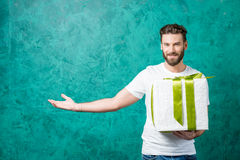 Man with a gift box. Handsome man in the white t-shirt holding gift box on the painted green wall background. Valentine`s Day concept Royalty Free Stock Images