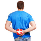 Man with a gift in hand. View from the back. Royalty Free Stock Image