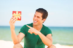 Man with gift. Handsome young man with gift at beach background Royalty Free Stock Image