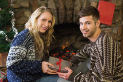 Man gifting woman in front of lit fireplace during Christmas Royalty Free Stock Image