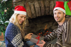 Man gifting woman in front of lit fireplace during Christmas Royalty Free Stock Images