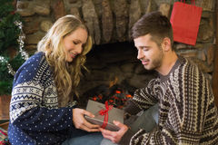 Man gifting woman in front of lit fireplace during Christmas Royalty Free Stock Photos