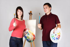 Man and girl artists standing near easel. Young man and girl standing near easel, holding brushes with palettes and smiling Royalty Free Stock Photo