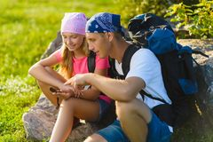Man and girl with backpack resting and looking at compass Stock Images
