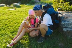 Man and girl with backpack resting and looking at compass Stock Image