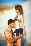 Man and girl on beach. In love couple on travel honeymoon vacation summer holidays romance. Young happy girl and handsome men kissing and hugging on ocean shore Stock Image