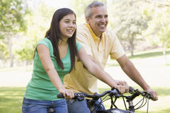 Man and girl on bikes outdoors smiling. Looking forward royalty free stock photos