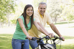Man and girl on bikes outdoors smiling Royalty Free Stock Photos
