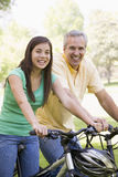 Man and girl on bikes outdoors smiling Stock Images