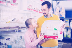 Man with the girl chose a bird  to buy. Smiling men with the girl chose a canary bird in the store to buy pet Royalty Free Stock Photo