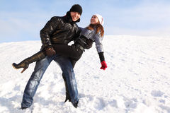 Man and girl dance on snowy area and smiling. Young man and girl dance on snowy area and smiling, man looking at camera Stock Images