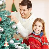 Man and girl decorating christmas tree. Together at home Royalty Free Stock Photo