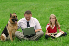 Man, girl and dog sitting. Man with laptop, girl with a book and dog sitting on the grass Stock Images