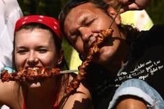 Man and girl eat a shish kebab. Summer, nature, the fried shish kebab, having a rest people Royalty Free Stock Image