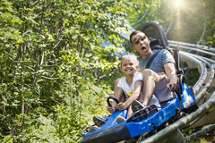 Man and girl enjoying a summer fun roller coaster ride. Smiling little girl and her dad riding downhill together on an outdoor roller coaster on a warm summer Royalty Free Stock Images