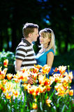 Man and girl among flowers. Lover man and girl among red yellow flowers in spring park Stock Photo