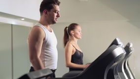 A man and a girl go on the treadmill. At the gym stock footage