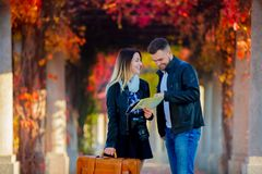 Man and girl help with navigation in the city for a tourist. Young men and girl help with navigation in the city for a tourist. Autumn season time stock photos