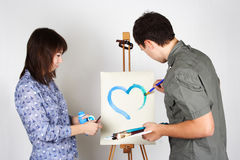 Man and girl holding painting blue heart Royalty Free Stock Images