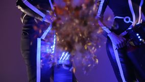 Man with a girl holds a machine for confetti. A shot by a confetti machine, a pipe sweeps the confetti and smoke into. The camera stock footage