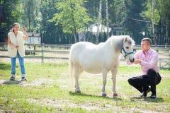 Man, girl and horse Stock Photos