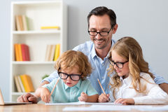 Man and girl how boy drawing. Very nice. Smiling mature men and pleasant girl looking how little cute concentrated boy drawing while sitting at the table Royalty Free Stock Images