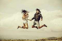 Man and girl jump high. Man and girl hipster couple in denim shorts jump high on mountain top on cloudy sky stock photo