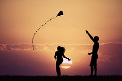 Man and girl with kite at sunset Royalty Free Stock Image