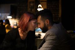 Man and the girl are leaning on their heads, showing love. In a pub Stock Image