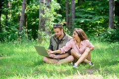Man and girl looking at laptop screen. Couple youth spend leisure outdoors with laptop. Modern technologies give. Opportunity to be online and work in any stock images