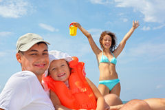 Man with girl in orange lifejacket and woman. Young man with little girl in orange lifejacket and beautiful woman with plastic toy bucket, woman lifted hands Stock Photo