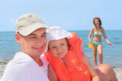 Man with girl in orange lifejacket and woman. Young man with little girl in orange lifejacket and beautiful woman with plastic toy bucket on beach Stock Photos